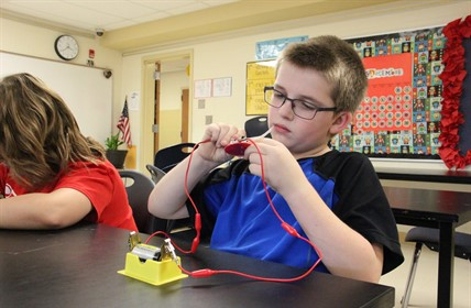 A student wires a battery-powered light.