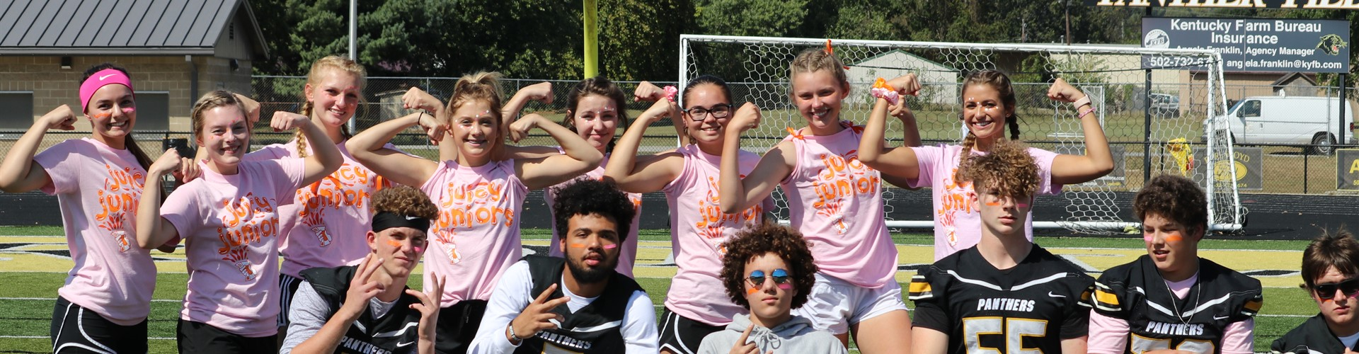 Row of girls in pink shirts flex behind row of boys in football jerseys.