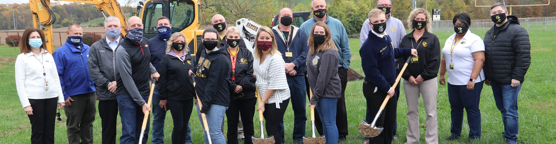 Group of masked people at groundbreaking. Five individuals hold shovels of dirt with row of people behind. Construction equipment in background.