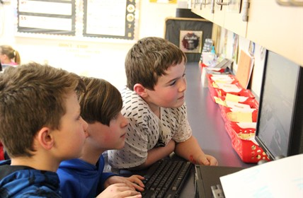 Three students using a computer.