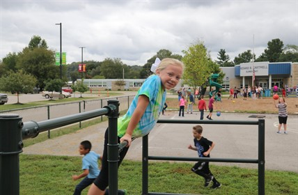 Student pushes up on monkey bars.