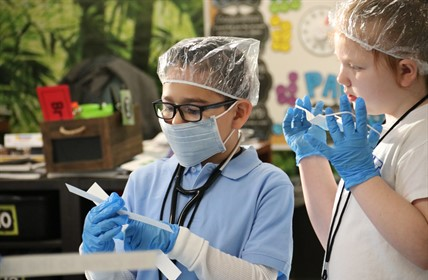 Elementary students wear surgical gear and replace pronouns with nouns in written sentences: