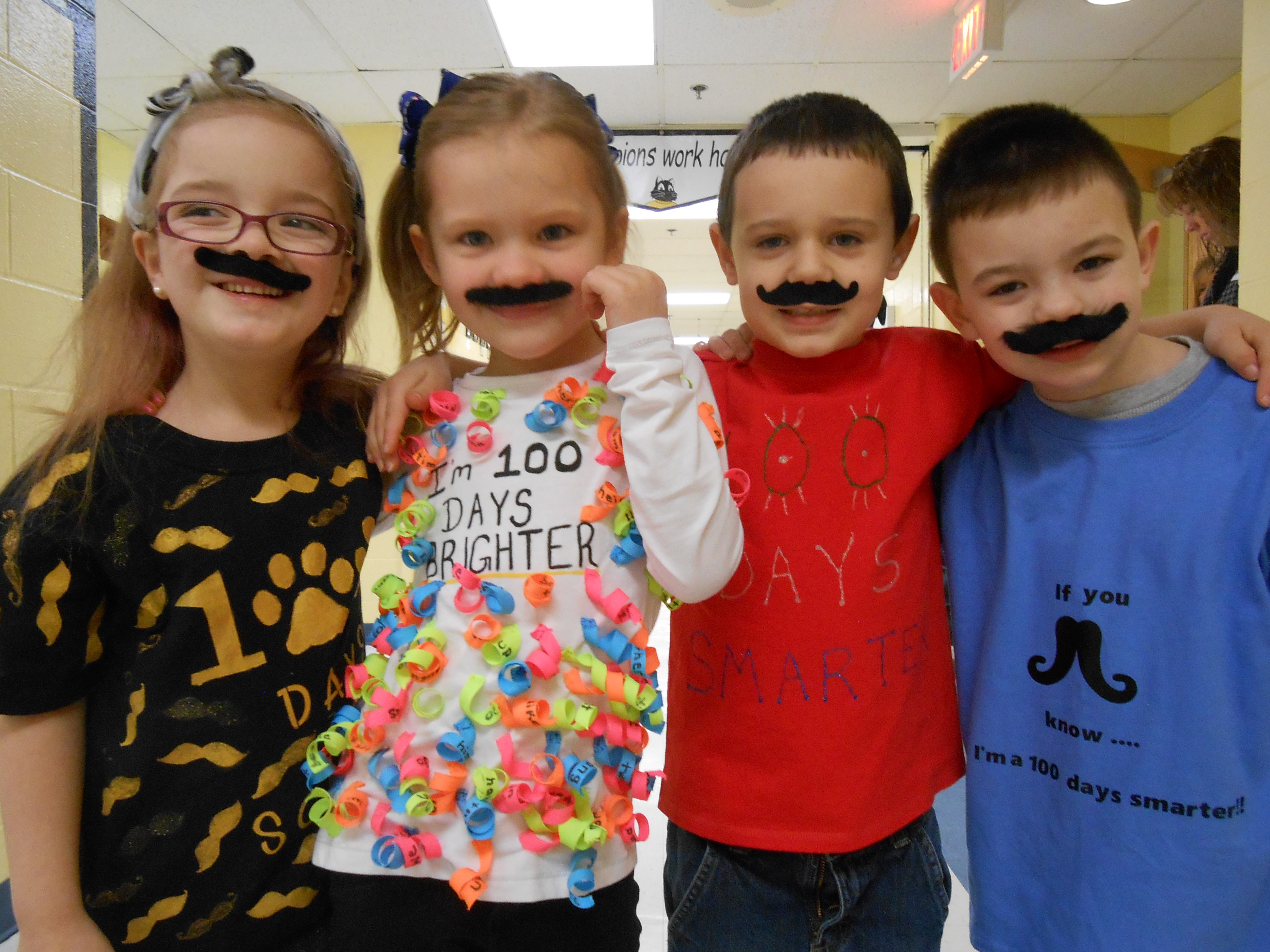 Three students wearing fake mustaches, 100th day of school