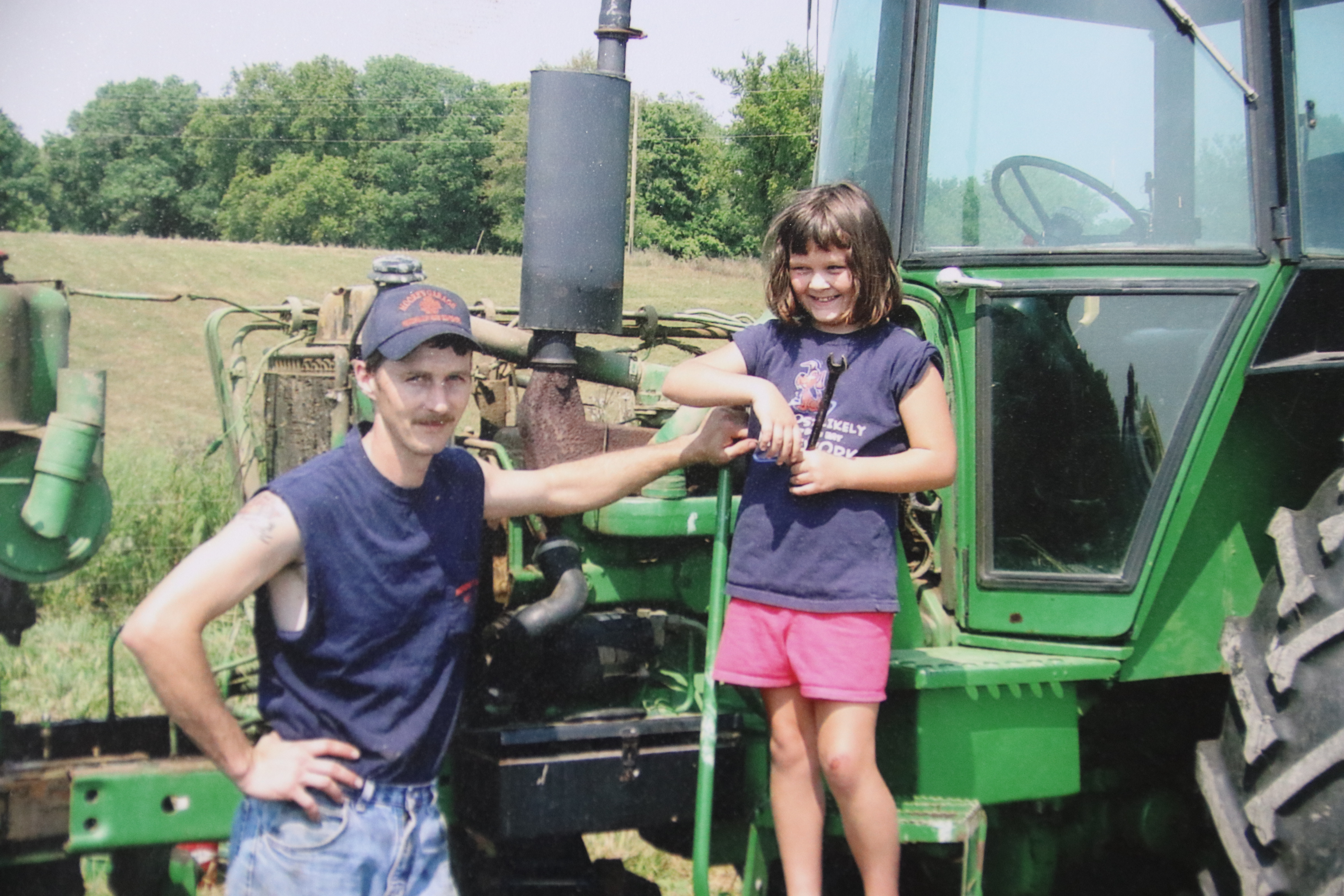 Moore and her father stand by a tractor