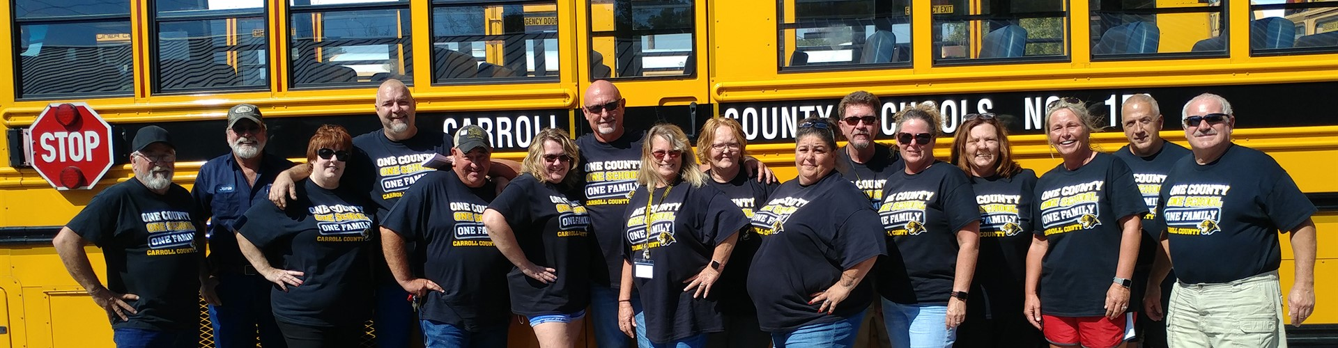 Sixteen bus drivers wear black shirts and stand together beside school bus.
